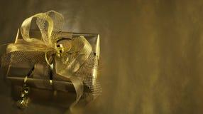 Caixa de presente dourada com decorações das quinquilharias Fotografia de Stock Royalty Free