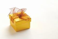 Caixa de presente dourada com laço marrom Imagens de Stock
