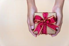 Caixa de presente dourada com o ribbow vermelho, dando a caixa de presente para a pessoa especial no dia especial fotografia de stock