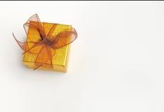 Caixa de presente dourada com opinião superior do laço marrom Fotos de Stock Royalty Free