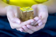 A caixa de presente dourada pôs sobre a sobreposição da mão do ` s da menina foto de stock royalty free