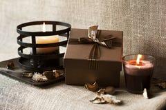 caixa de presente Dourado-marrom com velas na placa de madeira. Serapilheira/saco Imagens de Stock
