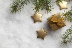 Caixa de presente e estrelas do Natal na neve Imagens de Stock