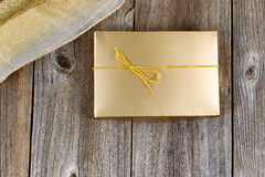 Caixa de presente e fita douradas brilhantes da cor em placas de madeira rústicas fotografia de stock royalty free