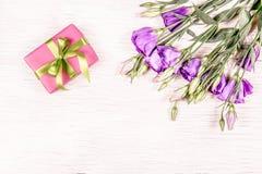 Caixa de presente e flores cor-de-rosa em um fundo de madeira branco Dia de matrizes Imagens de Stock