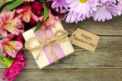 Caixa de presente e flores do dia de mãe na madeira Fotos de Stock