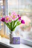 Caixa de presente e ramalhete macio de tulipas cor-de-rosa bonitas no vaso branco perto da janela com os pingos de chuva na luz d Imagem de Stock Royalty Free