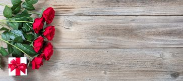 Caixa de presente e rosas vermelhas para a época natalícia especial em rústico foto de stock