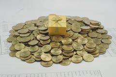 Caixa de presente em uma pilha de moedas de ouro Imagem de Stock