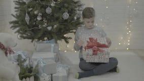Caixa de presente entusiasmado feliz do presente de Natal da abertura do rapaz pequeno na sala festiva decorada da atmosfera da á vídeos de arquivo