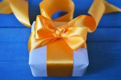 Caixa de presente envolvida com papel e curva do of?cio no fundo neutro com boke Conceito do feriado imagem de stock