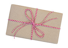 A caixa de presente envolvida no marrom reciclou o papel com corda vermelha e branca imagem de stock