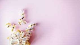 A caixa de presente envolvida no ouro listrou a fita no fundo cor-de-rosa pastel Nota vazia amarrada sobre Copie o espa?o foto de stock