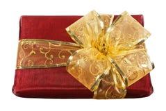 Caixa de presente envolvida vermelha com uma curva dourada grande Fotografia de Stock Royalty Free