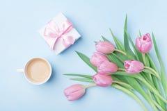 Caixa de presente, flores da tulipa e café na opinião de tampo da mesa pastel azul Cartão bonito da mola para o dia da mulher ou  Fotos de Stock Royalty Free