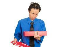 A caixa de presente mal-humorada da abertura do homem que olha a virada desagradou no que recebeu Fotografia de Stock