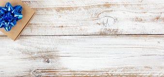 Caixa de presente no canto superior esquerdo para as épocas de férias na madeira rústica branca com abundância do espaço da cópia foto de stock royalty free