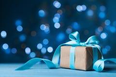 Caixa de presente ou presente do Natal com a fita da curva no fundo azul mágico do bokeh Copie o espaço para o cartão Imagem de Stock