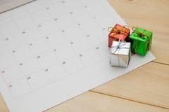 A caixa de presente pequena posta sobre a página do calendário tem o fundo de madeira Fotos de Stock