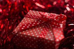 Caixa de presente pontilhada do Natal na decoração vermelha lustrosa Imagens de Stock Royalty Free