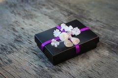 Caixa de presente preta com as flores brancas no fundo de madeira velho Fotos de Stock