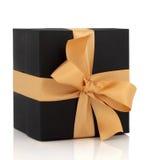Caixa de presente preta com curva do ouro fotografia de stock royalty free