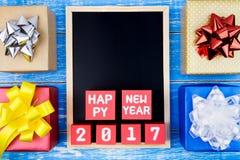 Caixa de presente, quadro-negro e número atuais do ano novo feliz 2017 em r Fotos de Stock Royalty Free