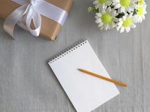 Caixa de presente, ramalhete das flores, bloco de notas de papel vazio com o lápis no fundo cinzento imagem de stock royalty free