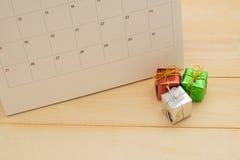 Caixa de presente três pequena que põe a parte dianteira do calendário sobre o backgro de madeira Imagens de Stock Royalty Free
