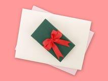 Caixa de presente verde com curva vermelha da fita e envelope branco com luz - cartão roxo no fundo cor-de-rosa Foto de Stock