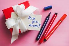 Caixa de presente vermelha amarrada com uma fita branca, os marcadores e um cartão com uma inscrição em um fundo cor-de-rosa fotos de stock