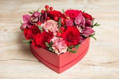 Caixa de presente vermelha com as flores na mesa de madeira imagens de stock