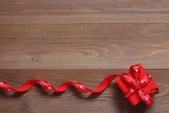 Caixa de presente vermelha com burocracias em um fundo de madeira Imagens de Stock Royalty Free