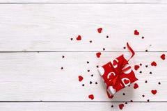 A caixa de presente vermelha com corações de papel no branco pintou pranchas de madeira foto de stock royalty free