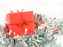 Caixa de presente vermelha com corda no assoalho de prata e no fundo branco Imagem de Stock