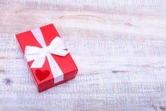 A caixa de presente vermelha com curva da fita abriu na tabela de madeira branca do vintage Fotografia de Stock Royalty Free