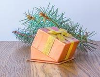 Caixa de presente vermelha com curva do ouro e árvore de Natal Imagem de Stock