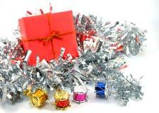Caixa de presente vermelha com os mini cilindros coloridos no fundo branco (foco Imagens de Stock Royalty Free