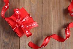 Caixa de presente vermelha com uma fita em um fundo de madeira Fotos de Stock