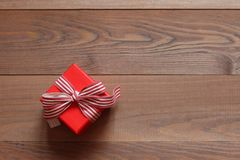 Caixa de presente vermelha com uma fita em um fundo de madeira Imagens de Stock