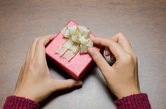 Caixa de presente vermelha decorada com fita dourada Fotos de Stock