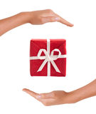 Caixa de presente vermelha entre as mãos Fotos de Stock Royalty Free