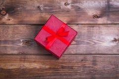 A caixa de presente vermelha envolvida no fundo de madeira pode usar-se no dia da mãe do dia de são valentim ou comemorar o dia d Fotografia de Stock Royalty Free