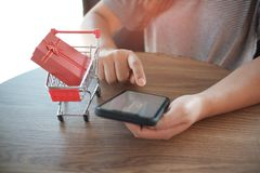 Caixa de presente vermelha no carrinho de compras com as mulheres que usam o telefone celular para o conceito de compra em linha foto de stock royalty free