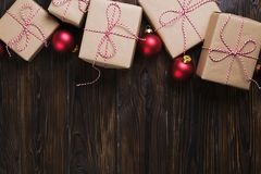 A caixa de presentes do Natal apresenta com as bolas vermelhas no espaço de madeira do texto da opinião superior do fundo Imagem de Stock