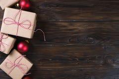 A caixa de presentes do Natal apresenta com as bolas vermelhas no espaço de madeira do texto da opinião superior do fundo Imagens de Stock