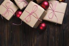 A caixa de presentes do Natal apresenta com as bolas vermelhas no fundo de madeira Imagem de Stock