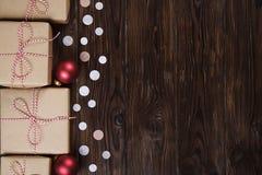 A caixa de presentes do Natal apresenta com as bolas vermelhas no fundo de madeira Imagens de Stock Royalty Free