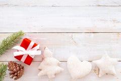 Caixa de presentes do presente de Natal e elementos vermelhos da decoração no fundo de madeira branco Fotos de Stock