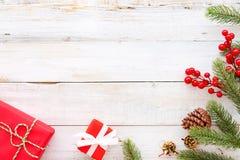 Caixa de presentes do presente de Natal e elementos vermelhos da decoração no fundo de madeira branco Imagens de Stock